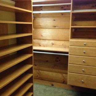 Imagen de armario vestidor unisex, rural, de tamaño medio, con armarios abiertos, puertas de armario de madera oscura y moqueta