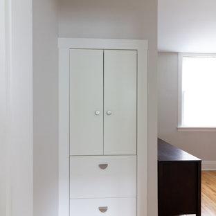 Diseño de armario vestidor unisex, escandinavo, con armarios con paneles lisos, puertas de armario blancas, suelo de madera clara y suelo amarillo