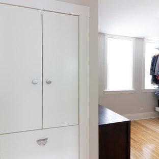 Ejemplo de armario vestidor unisex, escandinavo, con armarios con paneles lisos, puertas de armario blancas, suelo de madera clara y suelo amarillo