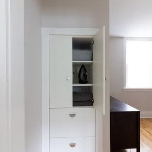 Diseño de armario vestidor unisex, nórdico, con armarios con paneles lisos, puertas de armario blancas, suelo de madera clara y suelo amarillo