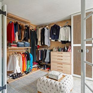 Ejemplo de vestidor unisex, clásico renovado, con armarios con paneles lisos, puertas de armario de madera clara y moqueta