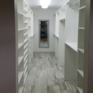 Design ideas for a mid-sized transitional gender-neutral walk-in wardrobe in Indianapolis with flat-panel cabinets, white cabinets and light hardwood floors.