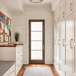 Foto di una cabina armadio unisex classica con ante in stile shaker, ante bianche e pavimento in legno massello medio