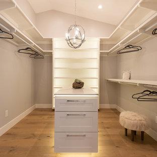 Cette image montre un dressing minimaliste de taille moyenne et neutre avec un placard à porte shaker, des portes de placard blanches et un sol en bois brun.