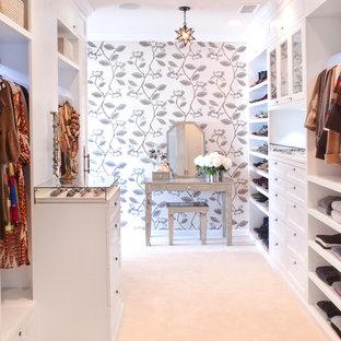 Immagine di una cabina armadio chic con ante bianche e moquette