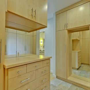 Imagen de vestidor unisex, retro, grande, con armarios con paneles lisos, puertas de armario de madera clara, suelo de pizarra y suelo beige