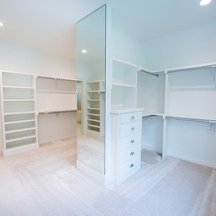Walk-in closet - farmhouse gender-neutral carpeted and beige floor walk-in closet idea in Raleigh with white cabinets