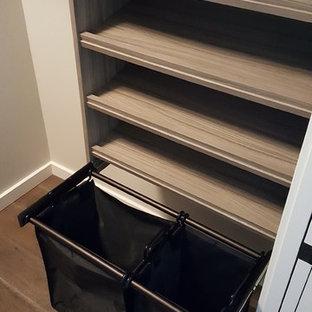 Foto di una cabina armadio unisex minimal di medie dimensioni con nessun'anta, ante in legno scuro e parquet scuro