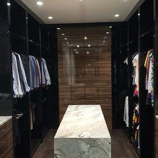 Esempio di una cabina armadio unisex contemporanea di medie dimensioni con ante lisce, ante in legno scuro, pavimento in legno massello medio e pavimento marrone