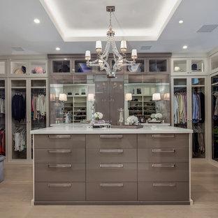 Modelo de armario vestidor unisex, contemporáneo, de tamaño medio, con armarios tipo vitrina, puertas de armario blancas, suelo de madera clara y suelo marrón