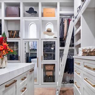 Diseño de armario vestidor tradicional renovado, extra grande, con armarios estilo shaker, puertas de armario grises, suelo de madera clara y suelo marrón
