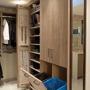 Foto de armario vestidor actual, grande, con armarios con paneles lisos, puertas de armario de madera clara y suelo de baldosas de porcelana