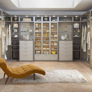 Ispirazione per un grande spazio per vestirsi unisex minimalista con ante lisce, ante bianche, parquet chiaro e pavimento beige