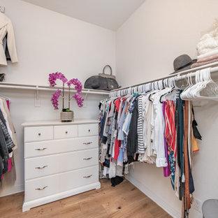 Ejemplo de armario vestidor de mujer, mediterráneo, extra grande, con armarios con paneles lisos, puertas de armario blancas, suelo de madera clara y suelo beige