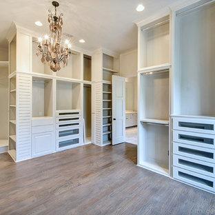 Mediterranes Ankleidezimmer mit Ankleidebereich, weißen Schränken und braunem Holzboden in Dallas