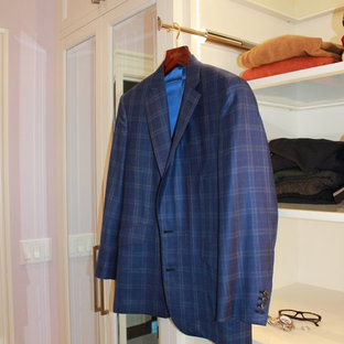 Modelo de armario vestidor unisex, actual, grande, con armarios con paneles empotrados, puertas de armario blancas y suelo de madera oscura