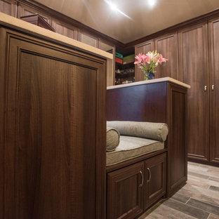 Esempio di una grande cabina armadio unisex tradizionale con ante con bugna sagomata, ante in legno scuro, pavimento in compensato e pavimento marrone