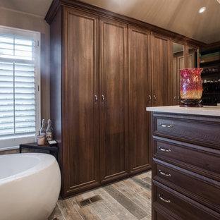 Ispirazione per una grande cabina armadio unisex chic con ante con bugna sagomata, ante in legno scuro, pavimento in compensato e pavimento marrone