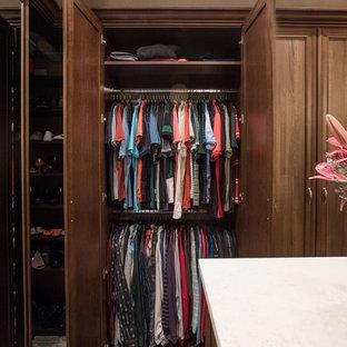 Idee per una grande cabina armadio unisex chic con ante con bugna sagomata, ante in legno scuro, pavimento in compensato e pavimento marrone