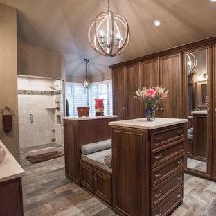 Cette photo montre un grand dressing chic neutre avec des portes de placard en bois brun, un sol en contreplaqué, un sol marron et un placard avec porte à panneau encastré.