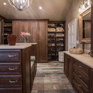デンバーの広い男女兼用トラディショナルスタイルのおしゃれなウォークインクローゼット (レイズドパネル扉のキャビネット、中間色木目調キャビネット、合板フローリング、茶色い床) の写真