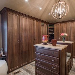 デンバーの大きい男女兼用トラディショナルスタイルのおしゃれなウォークインクローゼット (レイズドパネル扉のキャビネット、中間色木目調キャビネット、合板フローリング、茶色い床) の写真