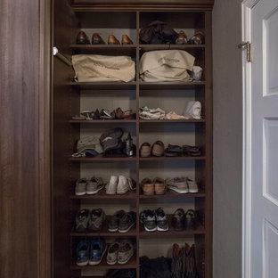 Diseño de armario vestidor unisex, clásico, grande, con armarios con paneles con relieve, puertas de armario de madera oscura, suelo de contrachapado y suelo marrón