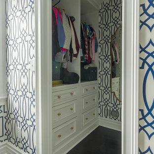 Foto de armario vestidor de mujer, tradicional, de tamaño medio, con armarios con paneles empotrados, puertas de armario amarillas, suelo de madera oscura y suelo marrón