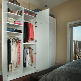 Modelo de armario de mujer, tradicional renovado, de tamaño medio, con armarios con paneles con relieve, puertas de armario blancas y suelo de madera oscura