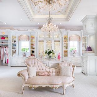 オーランドの広い女性用ヴィクトリアン調のおしゃれなフィッティングルーム (落し込みパネル扉のキャビネット、白いキャビネット、カーペット敷き、白い床) の写真