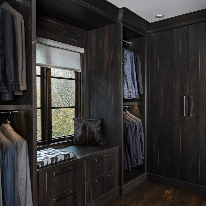 This walk-in closet, custom made with taupe flat slab cabinetry, is located off the master bath, creating a special sanctuary for the Him. Strong dark wood tones, sleek and modern, each and every cabi
