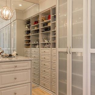 Diseño de armario y vestidor grande con armarios con paneles empotrados, puertas de armario grises, suelo de baldosas de porcelana y suelo negro