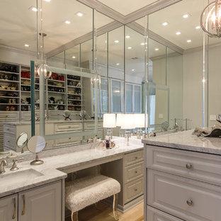 Imagen de armario y vestidor grande con armarios con paneles empotrados, puertas de armario grises, suelo de baldosas de porcelana y suelo negro