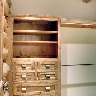 Modelo de armario vestidor unisex, rústico, de tamaño medio, con armarios con paneles empotrados, puertas de armario de madera oscura, moqueta y suelo beige