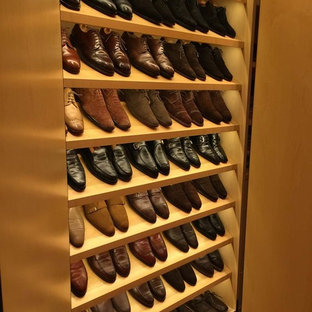This is an example of a large contemporary men's storage and wardrobe in New York with flat-panel cabinets and light wood cabinets.