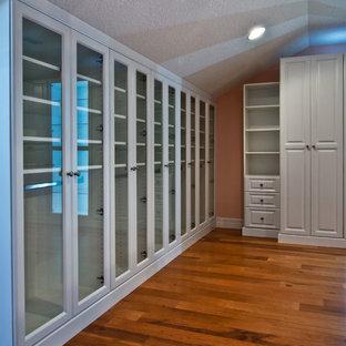 Foto de armario vestidor unisex, contemporáneo, grande, con armarios con paneles con relieve, puertas de armario blancas y suelo de madera en tonos medios