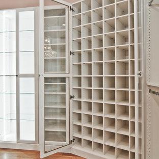オーランドの広い男女兼用トラディショナルスタイルのおしゃれなウォークインクローゼット (ガラス扉のキャビネット、白いキャビネット、無垢フローリング) の写真