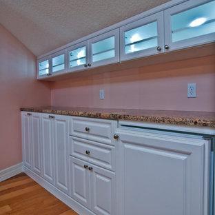 Modelo de armario vestidor unisex, clásico, grande, con armarios con paneles con relieve, puertas de armario blancas y suelo de madera en tonos medios