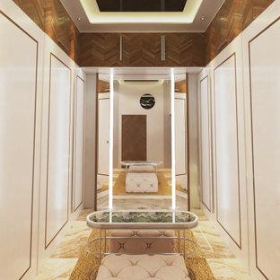 Ispirazione per una cabina armadio unisex minimal di medie dimensioni con ante lisce, ante bianche, pavimento in marmo, pavimento beige e soffitto in perlinato