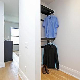 Modelo de armario vestidor unisex, nórdico, de tamaño medio, con armarios abiertos, puertas de armario de madera en tonos medios y suelo de madera clara