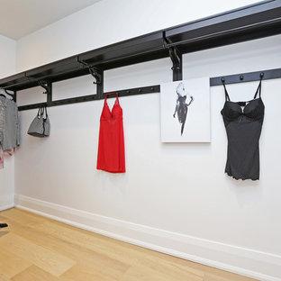 Imagen de armario vestidor unisex, escandinavo, de tamaño medio, con armarios abiertos, puertas de armario de madera en tonos medios y suelo de madera clara
