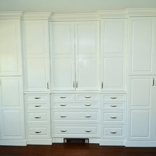 This is an example of a mid-sized traditional gender-neutral built-in wardrobe in New York with raised-panel cabinets, white cabinets and dark hardwood floors.