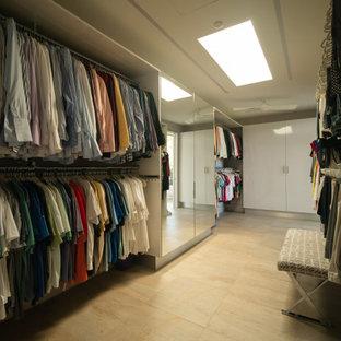 Modelo de armario vestidor unisex, moderno, grande, con armarios con paneles lisos, puertas de armario blancas, suelo de piedra caliza y suelo beige