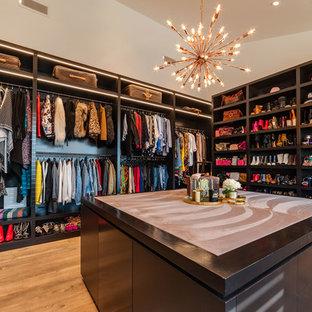 Idée de décoration pour un très grand dressing room design pour une femme avec un placard sans porte, des portes de placard en bois sombre et un sol en bois brun.