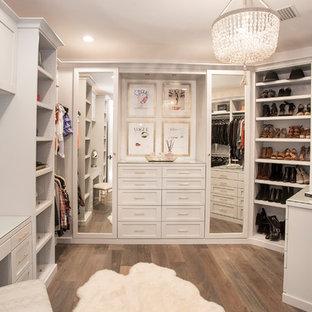 Ejemplo de armario vestidor costero con armarios estilo shaker, puertas de armario blancas, suelo de madera en tonos medios y suelo marrón