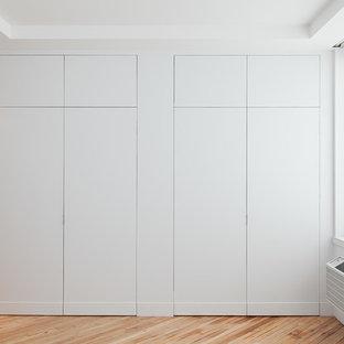 Diseño de armario contemporáneo con armarios con paneles lisos y puertas de armario blancas