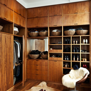 Contemporary gender-neutral storage and wardrobe in New York with flat-panel cabinets, dark wood cabinets and dark hardwood floors.
