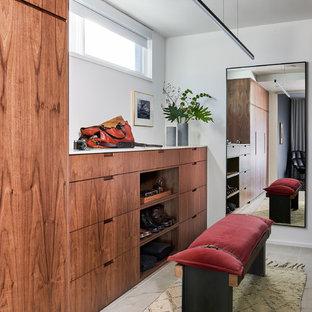 Idee per uno spazio per vestirsi unisex minimalista con ante lisce, ante in legno scuro e pavimento beige