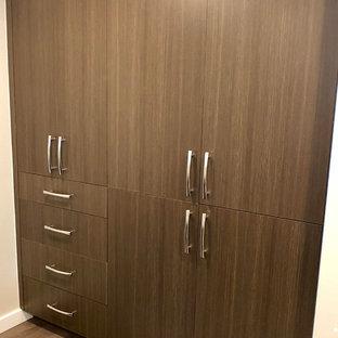 Idee per un armadio o armadio a muro unisex minimalista di medie dimensioni con ante lisce, ante con finitura invecchiata, pavimento in legno massello medio e pavimento marrone