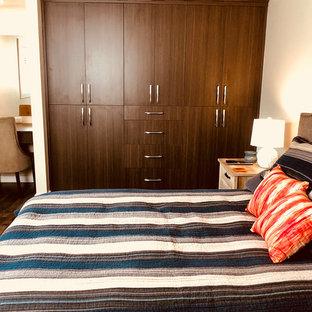 Immagine di un armadio o armadio a muro unisex minimalista di medie dimensioni con ante lisce, ante con finitura invecchiata, pavimento in legno massello medio e pavimento marrone